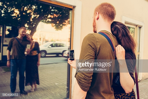 Caucasian couple taking self portrait in mirror
